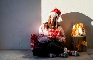 junge Frau in Weihnachtsmütze umgeben von Geschenken foto