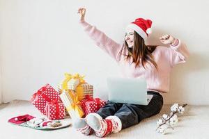 junge Frau in Weihnachtsmütze Online-Shopping umgeben von Geschenken foto