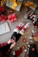 Draufsicht einer Frau in lustigen Socken, die Weihnachten zu Hause feiert foto