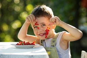 glücklicher Junge, der eine rote Johannisbeere hält foto