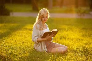 Mädchen sitzt im Gras und liest ein Buch foto