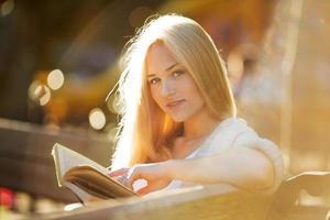 schöne Frau sitzt und liest ein Buch foto