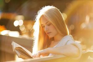 glückliches blondes Mädchen, das ein Buch liest foto