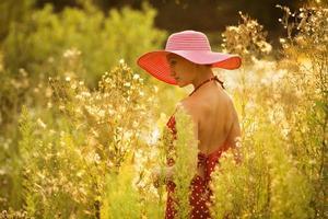 schöne Frau geht zwischen hohen Wildblumen foto