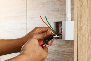 Elektriker isoliert elektrische Drähte in einer Plastikbox an einer Holzwand, um die Steckdose zu installieren. foto