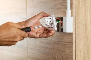 Ein Elektriker installiert mit einem Schraubendreher eine Steckdose in einer Plastikbox an einer Holzwand. foto