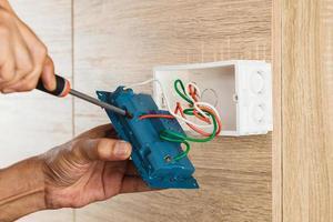 Die Hand eines Elektrikers verwendet einen Schraubendreher, um die Drähte an der Steckdose zu befestigen. foto