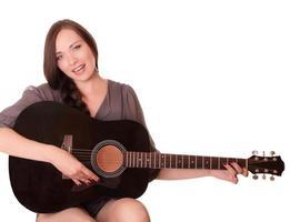schönes junges Mädchen sitzt mit Gitarre foto