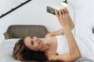 glückliche brünette junge frau, die zu hause handy verwendet. schönes Mädchen, das auf das Smartphone schaut und im Netz surft. lächelnde Frau, die auf ihr Handy schaut, während sie auf ihrem Bett liegt foto