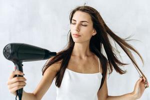 Porträt eines wunderschönen brünetten Mädchens, das Wind auf ihr nasses Haar bläst, während sie den Haartrockner in den Händen hält und ihre Augen mit Vergnügen schloss. Stockfotos foto