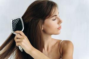 Verwicklungen loswerden. Porträt der schönen jungen Frau, die sich im Stehen ihr langes Haar bürstet und die Augen geschlossen hält foto