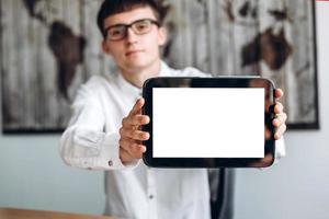 junger Mann mit Brille, der im Büro arbeitet und Tablet, Exemplar zeigt? foto