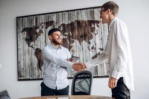 junger lächelnder Kerl, der seinem Geschäftspartner die Hand schüttelt foto