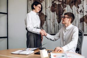 junge Geschäftsleute haben einen Deal, sie geben sich die Hand foto