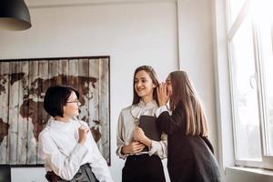 Konzept der Arbeit, kontroverse Themen. Drei selbstbewusste Mädchen unterhalten sich im Büro, die eine flüstert der anderen ins Ohr foto