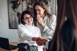 lächelndes Mädchen mit Brille schüttelt ihrer Kollegin die Hand, während ihre Assistentin etwas in ihr Ohr sagt foto