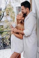 Mann umarmt schwangere Frau im Bademantel auf Balkon foto
