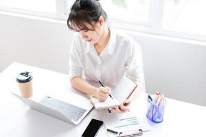 Porträt einer jungen Geschäftsfrau, die in einem Notizbuch sitzt und Pläne macht foto