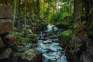 Bach fließt zwischen moosbedeckten Felsen foto