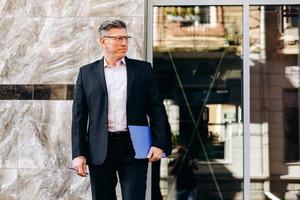 Porträt eines ernsten älteren Mannes im Anzug, der ein Papier im Freien steht und hält. - Bild foto
