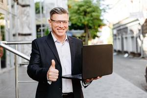 glücklicher Geschäftsmann, der offenen Laptop hält und mit Daumen nach oben lächelt foto