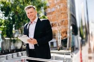 Porträt des fröhlichen leitenden Geschäftsmannes schreiben eine Notiz und schauen in die Kamera. foto