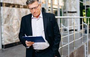 Senior Geschäftsmann mit Brille liest aufmerksam Dokument - Bild foto