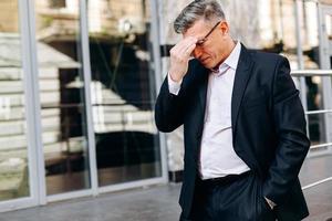 älterer Mann berührt seinen Kopf mit der Hand. - Konzept Kopfschmerzen, Bild foto