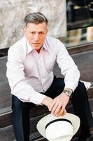 Ernster Mann, der auf dem Bürgersteig sitzt und einen Hut in den Händen hält und in die Kamera schaut. - Bild foto