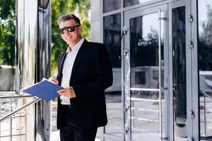 Porträt eines glücklichen leitenden Geschäftsmannes mit Sonnenbrille, der ein Dokument hält. - Bild foto
