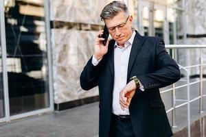 Geschäfts-, Pünktlichkeits- und Personenkonzept - leitender Geschäftsmann, der die Zeit auf der Uhr auf seiner Hand in der Stadt überprüft foto
