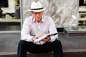 älterer Mann mit Hut, der auf dem Bürgersteig sitzt und ein Notizbuch in den Händen hält - Bild foto