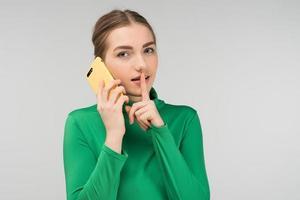 hübsche junge Frau, die auf einem Handy spricht, das es in ihren Händen hält. zum Schweigen rufen foto