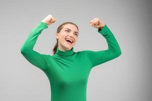 glückliche, fröhliche junge Frau, die mit den Händen nach oben schaut und mit offenem Mund lächelt foto