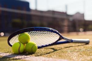 drei Tennisbälle und Schläger auf Hartplatz unter Sonnenlicht foto