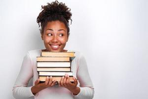 Porträt des jungen Mädchens des glücklichen Nerds, das Bücher über weißem Hintergrund hält. zurück zur Schule foto