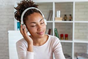 Porträt eines entzückenden Mädchens mit geschlossenen Augen in Kopfhörern, das Musik hört - Bild foto