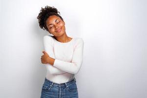 charmante Mulattin umarmt sich selbst und fühlt sich wohl und gelassen .- image foto