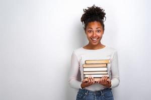 Porträt eines aufgeregten jungen Mädchens, das Bücher über weißem Hintergrund hält. zurück zur Schule foto