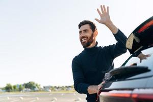 Porträt des gutaussehenden Kaukasiers, der die Mikrofaser in der Hand hält und das Auto poliert, während er jemandem auf der Straße zuwinkt foto