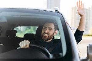 Hallo sagen. hübscher junger lächelnder Geschäftsmann, der in einem neuen Auto sitzt und jemandem zuwinkt, während er das Auto mit Freudengefühlen fährt foto