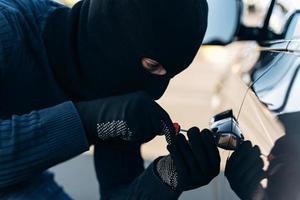 Nahaufnahme des gefährlichen Mannes, der in Schwarz mit einer Sturmhaube auf dem Kopf gekleidet ist und beim Stehlen das Schloss mit einem Pick knackt. Autodieb, Autodiebstahlkonzept foto