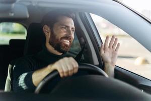 hübscher junger lächelnder fahrer des autos, der die hand als grußzeichen winkt, während er das auto mit freudengefühlen fährt. Transportkonzept foto