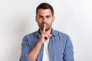 Mann in Freizeitkleidung, der mit dem Finger im Studio auf Stille gestikuliert foto