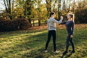 Fitness im Freien, zwei Mädchen, die Händchen halten, einander gegenüberstehen. foto