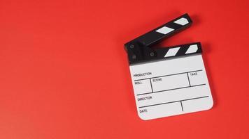 Filmklappe oder Filmtafel. Es wird in der Videoproduktion, Film- und Kinoindustrie auf rotem Hintergrund verwendet. foto