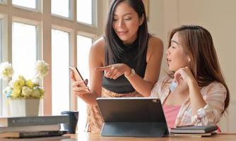 Zwei Mädchen im Teenageralter mit Kreditkarten in der Hand wählen Artikel vom Smartphone aus, Online-Shopping-Ideen. foto