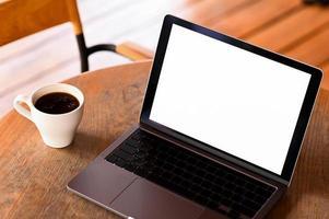 Mockup-Laptop mit leerem Bildschirm und Kaffee auf dem Tisch, aus der Draufsicht. foto