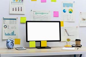 Computer leerer Bildschirm mit leerem Klemmbrett, Uhr und Taschenrechner mit Bürobedarf, Kaffeetasse zum Mitnehmen auf dem Schreibtisch, Datendiagramm und Notizpapier an der Bürowand. foto