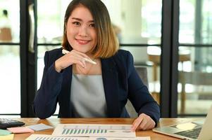 Die junge Geschäftsfrau im Anzug schaut in die Kamera und lächelt foto